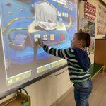 Chłopiec trzymający w ręku interaktywny pisak i wykonujący zadanie na tablicy multimedialnej.