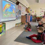 Grupa dzieci siedzących na dywanie i oglądajaca bajkę na tablicy multimedialnej.