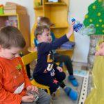 Troje dzieci siedzących na krzesełkach. Chłopiec siedzący po środku wrzuca do żóltego worka plastikową butelkę. Chłopiec po lewej stronie trzyma w ręku słoik.