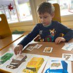 Chłopiec siedzący przy stoliku i przyporządkowujący obrazki różnych przedmiotów do właściwych pojemników.