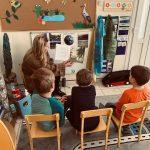 Troje dzieci siedzących na krzesłach i słuchających bajki czytanej przez nauczycielkę.