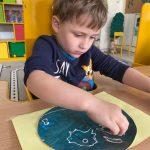 Chłopiec siedzący przy stoliku i wykonujący pracę plastyczną - planetę Ziemię.