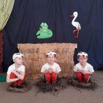 Trzech chłopców przebranych za bociany i siedzacych w bocianich gniazdach. W tle znajduje się wiosenna dekoracja.