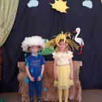 Chłopiec przebrany za chmurkę ora zstojąca obok niego dziewczynka przebrana za słoneczko. W tle znajduje się wiosenna dekoracja.