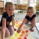 Dwie dziewczynki klęczące na dywanie i odbijające pomalowane farbą dłonie na brystolu.