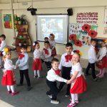 Grupa dzieci tańcząca w parach. Z przodu stoi w kółku troje dzieci. Przedszkolaki ubrane są na galowo. Chłopcy mają pod szyją czerwone kokardy, dziewczynki na głowach kolorowe wianki.
