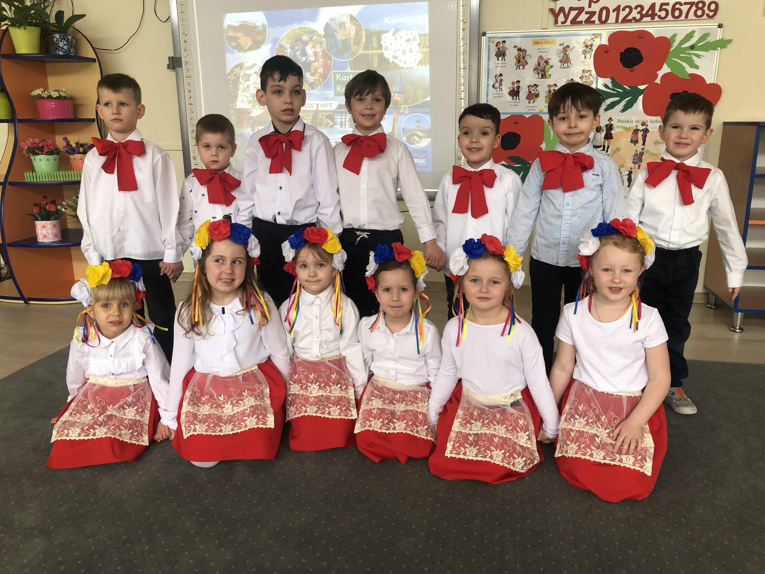 Grupa dzieci pozująca do zdjęcia w sali przedszkolnej, w dwóch rzędach. W pierwszym rzędzie dziewczynki mają na głowach kolorowe wianki. Chłopcyi stojacy w drugim rzędzie mają pod szyją czerwone kokardy.