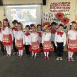Grupa dzieci pozująca do zdjęcia w sali przedszkolnej, ustawiona w rzędzie. Dziewczynki mają na głowach kolorowe wianki, chłopcy pod szyją czerwone kokardy. Dziewczynki mają równe stroje: białe bluzki oraz czerwone spódniczki, chłopcy białe koszule oraz czarne spodnie.