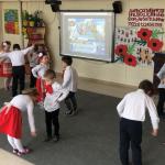 Grupa dzieci tańcząca w parach w sali przedszkolnej. Dziewczynki mają na głowach kolorowe wianki, chłopcy pod szyją czerwone kokardy. Dziewczynki mają równe stroje: białe bluzki oraz czerwone spódniczki, chłopcy białe koszule oraz czarne spodnie.i ubrane są urzoczyście,