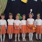 Sześcioro dziewczynek stojacych w jednym rzędzie, ubranych w białe buzki i pomarańczowe spódniczki. Na głowach mają wiosenne opaski. W tle znajduje się ilustracja bociana, żaby, drzewa, słońca oraz chmurek.