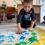 Chłopiec klęczący na dywanie i odbijajacy pomalowaną na niebiesko dłoń na brystolu.