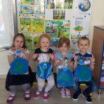 Czworo dzieci trzymajacych w rękach prace plastyczne planetę Ziemię.