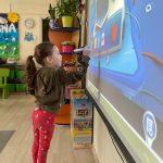 Dziewczynka stojaca przed tablicą interaktywną, trzynająca w ręku pisak i wykonująca zadanie na tablicy