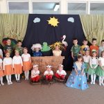 Grupa dzieci ubrana w wiosenne stroje. Dziewczynki po lewej stronie maja ubrane białe bluzki i pomarańczowe spódniczki. Dziewczynki po prawej stronie białe bluzki i zielone spódniczki. Po środku w gnieździe siedzi trzech chłopców przebranych za bociany. Obok nich po prawej stronie siedzi dziewczynka przebrana za Panią Wiosnę. Za bocianami stoi dziewczynka przebrana za słoneczko i chłopiec przebrany za chmurkę. W tle znajduje się wiosenna scenografia.