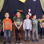 Sześcioro chłopców stojących w jednym rzędzie. Chłopiec stojący po środku ma nad głową parasol. W tle widać ilustrację bociana, drzew i słoneczka.