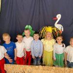 Ośmioro dzieci stojących w jednym rzędzie. Po środku stoi dziewvczynka przebrana za słoneczko. W tle znajduje się ilustracja żaby i bociana.