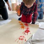 Chłopiec siedzacy na dywanie i odbijający pomalowaną na pomarańczowo dłoń na brystolu. W tle, po lewej stronie klęczy Pani, po prawej stronie chłopiec.