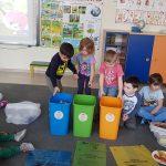 Grupa dzieci siedząca na dywanie w sali przedszkolnej. Troje dzieci stoi za pojemnikami służącymi do segregacji śmieci. Przed pojemnikami znajdują sie worki do segregacji śmieci. Po lewej i prawej stronie, w workach znajduja się śmieci.