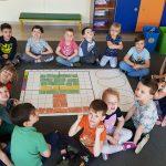 Dzieci siedzące w kole na dywanie w sali przedszkolnej. Pi środku koła znajduje sie mata na której ułożone są fiszki przedstawiające drzewo.