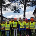 Grupa dzieci stojąca w dwóch rzędach w ogrodzie przedszkolnym, majacych ubrane kamizelki odblaskowe.