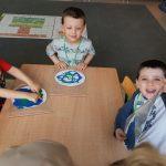 Troje dzieci siedzących przy stoliku i wykonujących prace plastyczne - planetę Ziemię.