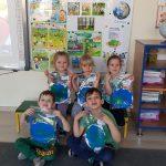 Pięcioro dzieci trzymających w rękach wykonane przez siebie prace plastyczne - planetę Ziemię.