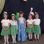 Pięć dziewczynek stojących w jednym rzędzie. Dziewczynka stojąca po środku przebrana jest za Panią Wiosnę, Dziewczynki stojące po bokach mają ubrane białe bluzki i zielone spódniczki. Na głlowach mają założone wiosenne opaski.