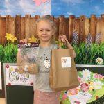 Dziewczynka trzymająca w rękach nagrody zdobyte podczas konkursu. W lewej ręce papierową torbę, w prawej ręce pluszaka.