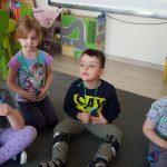 Czworo dzieci siedzących na dywanie w sali przedszkolnej i pokazujących zawieszone na szyi medale.