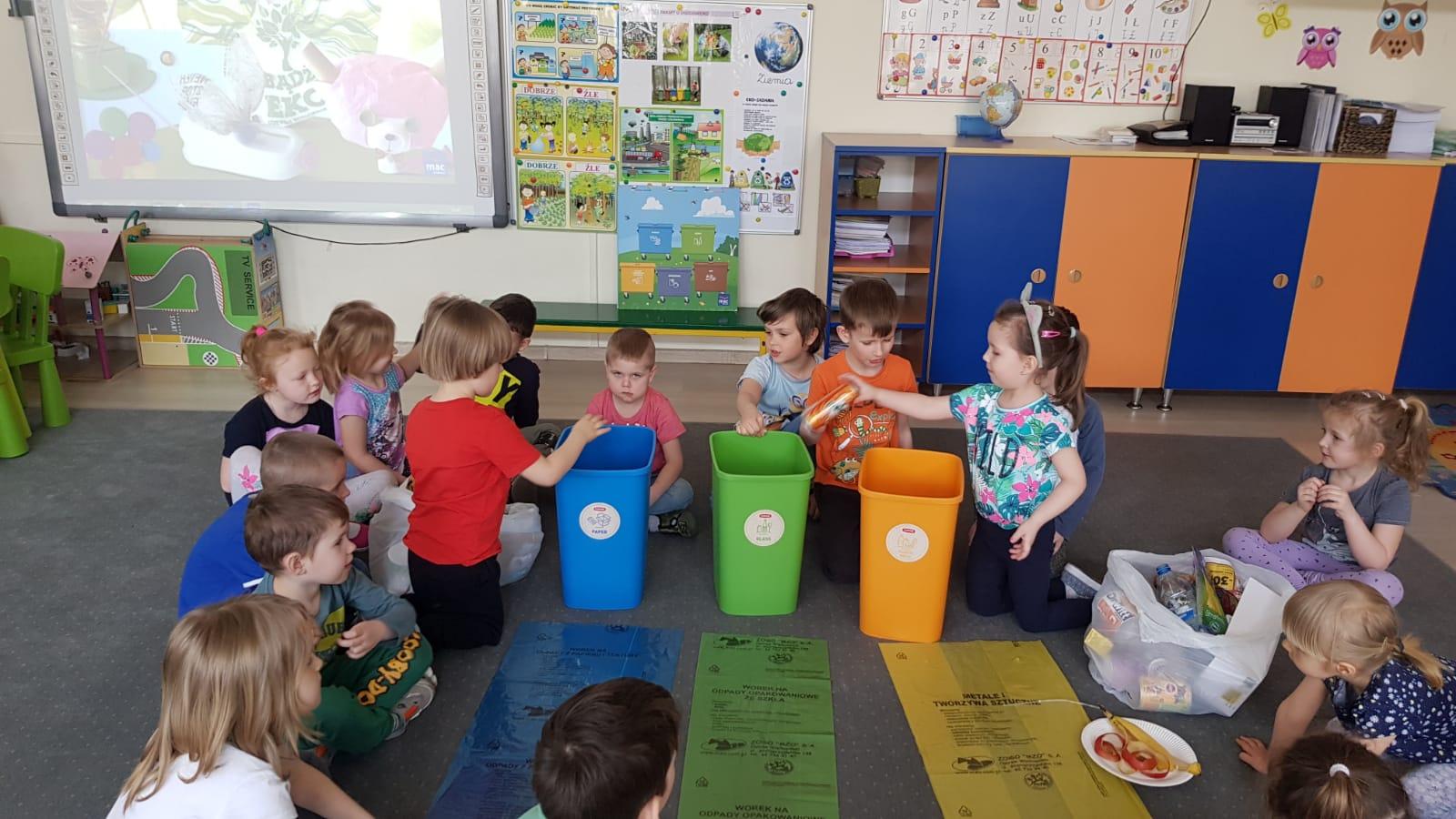 Grupa dzieci siedzących na dywanie w sali przedszkolnej. Po środku stoją trzy pojemniki do segregacji śmici, przed którymi leżą worki. Dziewczynka po prawej stronie wrzuca do pojemnika puszke po napoju. Po prawej i lewej stronie pojemników znajdują się worki, w których znajduja się nieposegregowane śmieci.