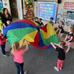 Dzieci wraz z Pania stojący w kole i trzymający w rękach kolorową chustę.