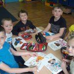 Dzieci siedza przy stole i kolorują kolorowankę