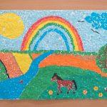 Praca plastyczna: wyklejanka przedstawia konia na polu, w tyle tęcza, słońce, rzeka.