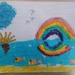 """Praca plastyczna"""" wyklejanka przedstawia tęczę, wodę z rybami, chmury."""