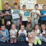 Dzieci stoją w dwóch rzędach. W rękach trzymają wycięte z papieru dłonie. Jedno dziecko trzyma pluszowego misia.