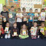 Dzieci ustawione są w 2 rzędach. W rękach trzymają kartki które same wykonały.