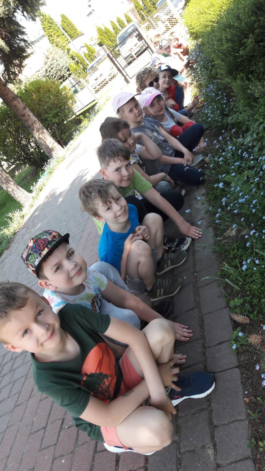 Dzieci kucają wzdłuż chodnika. Obok posadzone są niezapominajki.