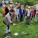 Dzieci stoją w grupie na trawie. Przed nimi rozrzucone są obrazki pająków. Jedno dziecko trzyma w ręce łapkę na muchy i schyla się do obrazków.