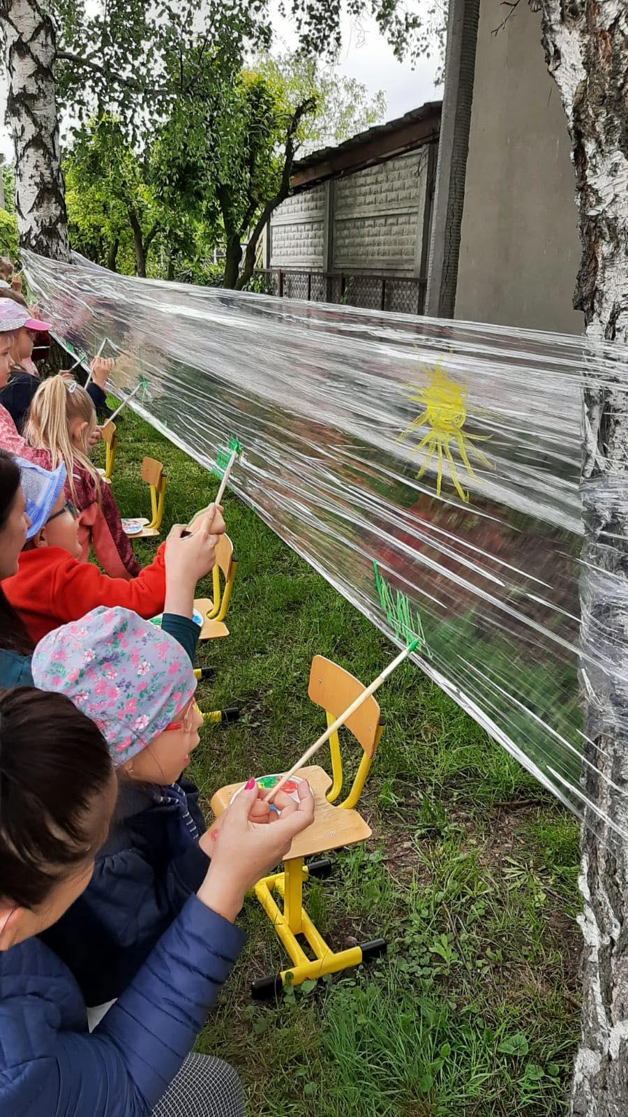 Dzieci na dworze malują farbami na folii zawieszonej pomiędzy 2 drzewami.