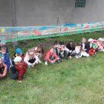 Duża grupa dzieci kuca na trawie. Nad nimi na folii rozciągniętej między drzewami jest namalowany obrazek.