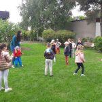 Dzieci stoją na trawie w rozsypce.