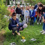 Dzieci stoją w grupie na trawie. Przed nimi rozrzucone są obrazki pająków. Jedno dziecko trzyma w ręce łapkę na muchy i schyla się do obrazków. Dziecko z łapką jest trzymane przez Pania.