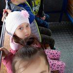 Czworo dzieci siedzących na ławce w kolejce turystycznej.