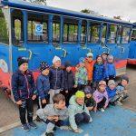 Grupa dzieci pozująca do zdjęcia w dwóch rzędach przed kolejką turystyczną.