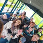 Grupa dzieci wraz z siedmioma Paniami przemieszczających sie w kolejce turystycznej.
