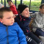 Pięcioro dzieci siedzacych w kolejce turystycznej.