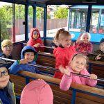 Grupa dzieci wraz z Panią siedzący w kolejce turystycznej.