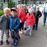 Grupa dzieci stojących w parach w ogrodzie przedszkolnym. Z tyłu, obok dzieci stoi Pani.