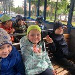 Siedmioro dzieci siedzących w kolejce turystycznej na dwóch ławkach.