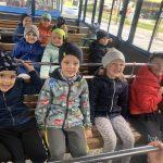 Grupa dzieci jadacych kolejką turystyczną, siedzacych w trzech ławkach.